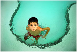 A boy in a children's swimming pool.